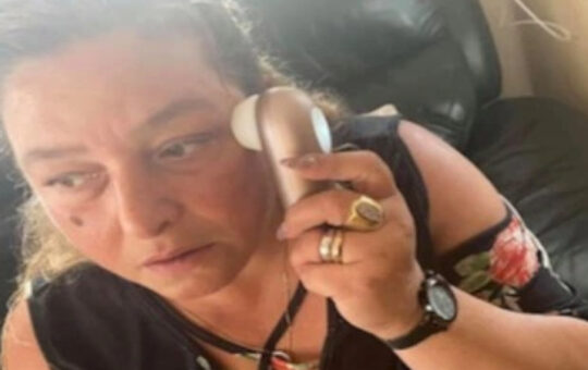 Woman using vibrator on face